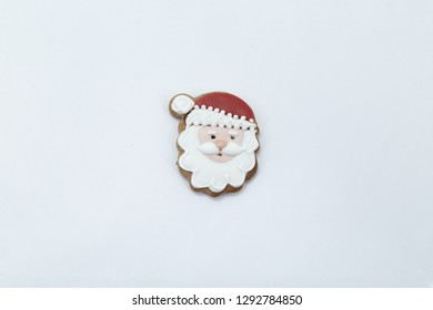 Beautiful Christmas gingersnap in the form of Santa Claus's head on a white background