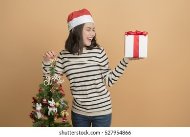 Beautiful christmas girl in santa hat with boxes  on autumn background.