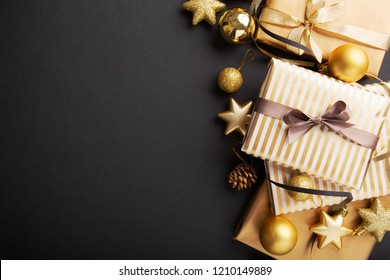 Beautiful christmas golden silver deco baubles with gifts on dark black background. Flat lay design. Copy Space. Horizontal.