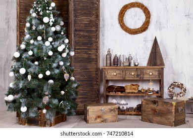 Beautiful Christmas interior. New year decoration. Christmas tree with a wood chests.