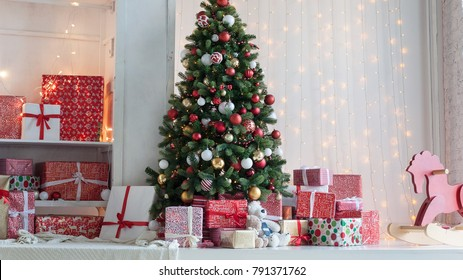 Beautiful Christmas interior with Christmas tree and gifts around it in white and red tones
