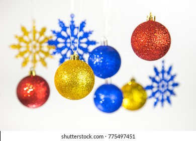 Beautiful Christmas and New Year colorful background. Close up of red, blue, golden shining festive balls hanging on glossy silver ropes isolated on white. Horizontal color phtography.
