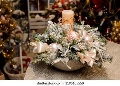 Beautiful Christmas table composition in vase made of fir tree covered with artificial snow, beige balls and bows, candle and beads against the festive interior