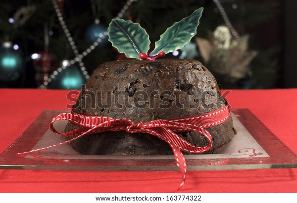 Beautiful Christmas table setting in front of Christmas Tree, featuring a classic plum pudding with holly on red tablecloth.