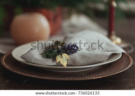 beautiful christmas table setting with sackcloth rustic napkin, candle and fir tree, close up