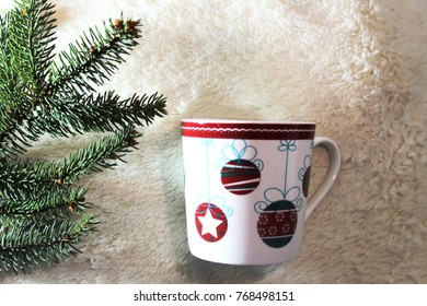 Beautiful christmas tea cup, fir tree leaves, decorated on a white cushion, christmas time (selected focus)