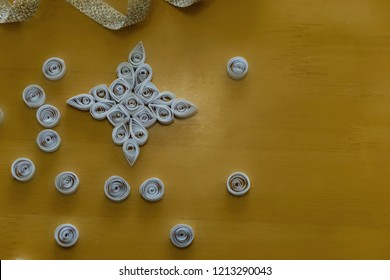 Beautiful Christmas tree decoration, white snowflake, quilling, made of thin white strips. Concept hobby, homemade decoration.