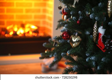 beautiful Christmas tree with decorations on a background of a burning fireplace, room, new year, Christmas, holiday, Christmas tree toy in red and gold, the light from the fireplace