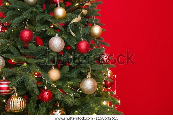 Beautiful Christmas tree with fairy lights and festive decor on red background