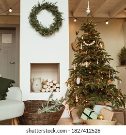 Beautiful Christmas tree, wreath frame, gift boxes in cozy comfortable living room. Festive Christmas / New Year holidays celebration decorations in modern home interior design with sofa and carpet.