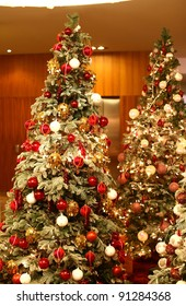 Beautiful Christmas trees with wonderful rich and colorful ornaments in a hall