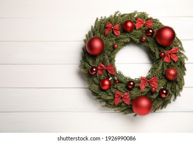 Beautiful Christmas wreath on white wooden background, top view. Space for text