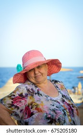 Beautiful chubby elderly woman in a pink hat on vacation at sea