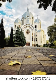 beautiful church in autumn with coloured leaves on the path