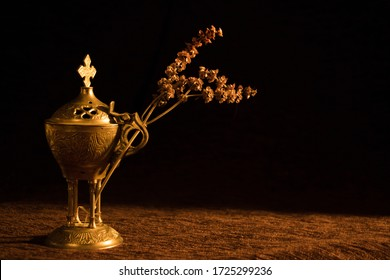 A beautiful church censer with a dried branch with a dark background