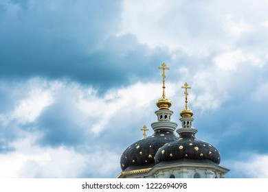 Beautiful church domes with gold crosses against a cloudy sky on a cloudy day.