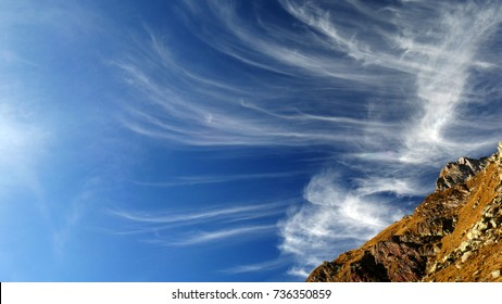 beautiful cirrus clouds in a blue sky in a sunny autumn day in the Orobie mountains, Italy.