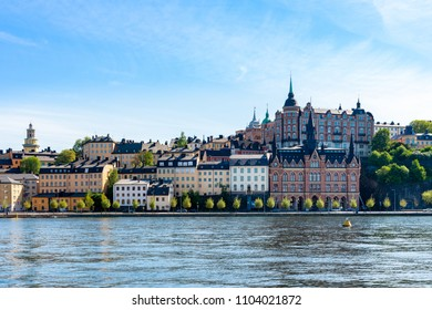 Beautiful city architecture by the water. Old buildings against summer sky.