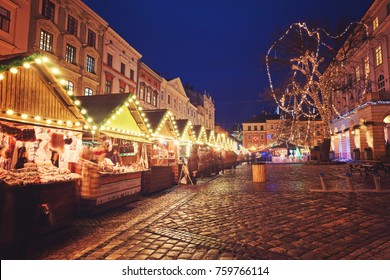 beautiful city center and wooden cabins for market covered in snow. snowy town square in Lviv. european city before christmas holidays