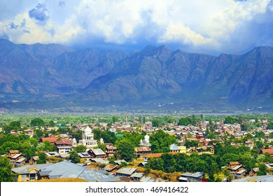 Beautiful city scape - traditional kashmiri houses, sikh temple in green valley against the background of colorful mountain range and cloudy sky in Srinagar, Himalayas, Jammu & Kashmir, Northern India