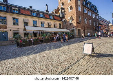 Beautiful city street view. Walking peple and people sitting in outdoor restaurant. Uppsala. Sweden. 06 06 19.