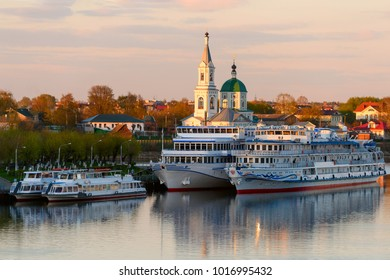 Beautiful city Tver landscape view of orange sunset, docked ships on river Volga and Catherine's convent with sky, green trees and old russian buildings. Small city architecture concept. Tver, Russia.