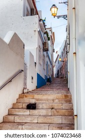 Beautiful cityscape, black cat sitting on the steps in the old town of Albufeira, Portugal, Algarve