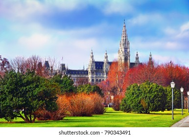 Beautiful cityscape - green lawn, colorful trees and bush at the background of Vienna city hall and cloudy blue sky - view from Heroes square in Austria, Central Europe