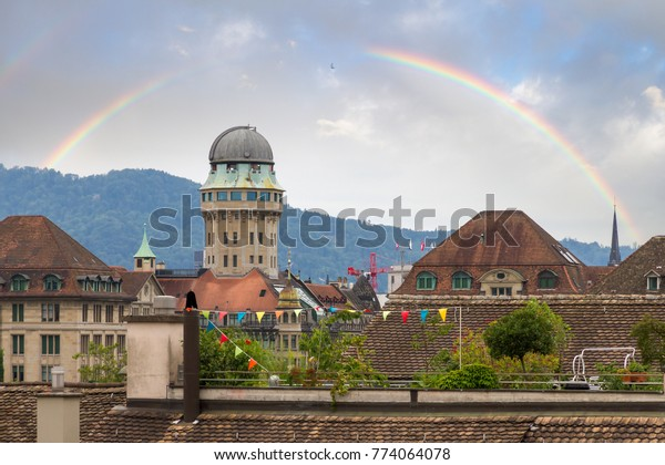 Beautiful cityscape looking towards the Urania Sternwarte observatory telescope in Zurich, Switzerland, with a beautiful rainbow in summer