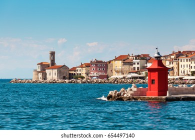 Beautiful cityscape of the old city Piran with historical medieval and new red lighthouses in summer.