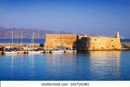 Beautiful cityscape - old venetian port, ancient Koules fort, yachts on the background of bright blue sea water and sky at evening, harbour of Heraclion, island of Crete, Greece, Southern Europe