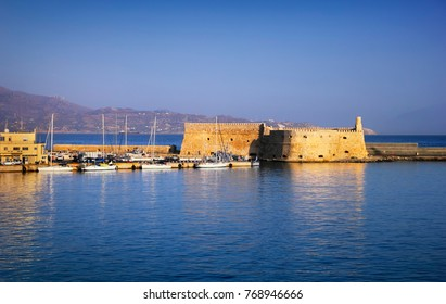 Beautiful cityscape - old venetian port, ancient Koules fort, yachts on the background of bright blue sea water and sky at evening, harbor of Heraclion, island of Crete, Greece, Southern Europe