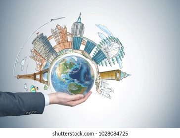Beautiful cityscape on a gray wall. Watercolor like style. Abstract. Man holding a globe. Elements of this image furnished by NASA