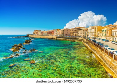 Beautiful cityscape of Ortygia (Ortigia), the historical center of Syracuse, Italy. Skyline of a European coastal town with turquoise transparent water and picturesque clouds in the sky