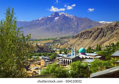 Beautiful cityscape - traditional houses and mosque with emerald green cupola against the background of mountain range and blue sky in Kargil city, Himalayas, Ladakh, Jammu & Kashmir, Northern India