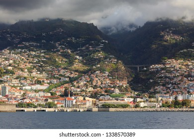 Beautiful cityscape view of the city Funchal, Madeira, seen from the Atlantic ocean, with ominous clouds