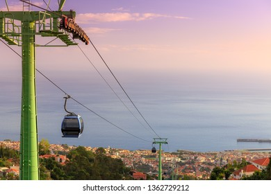 Beautiful cityscape view over the city of Funchal, Madeira,  with the cable car going up Monte Funchal, at sunset