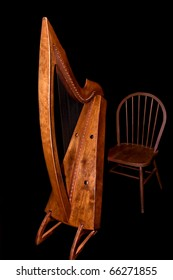 A beautiful classic celtic harp and chair against a black background.