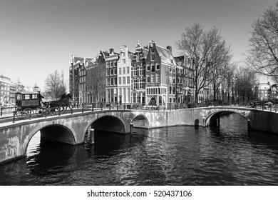 Beautiful classic view of the famous UNESCO world heritage canals of Amsterdam, the Netherlands, in black and white. Keizersgracht (Emperors canal) with horse carriage.