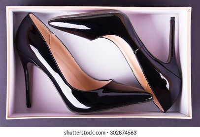 Beautiful classic women shoes on high heels in a box on a black background. Ideal for blogs or magazines.
