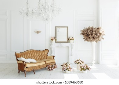 beautiful classical white interior with a fireplace, brown sofa and a vintage chandelier. Retro, classics horizontal view