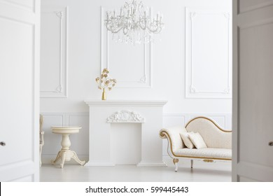 Beautiful Classical White Interior With A Fireplace, A Sofa And A Vintage  Chandelier. Retro