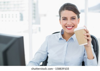 Beautiful classy brown haired businesswoman enjoying coffee in bright office