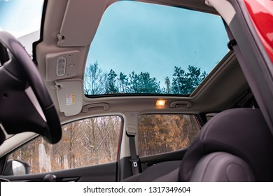 Beautiful clean luxury interior of a modern korean suv with big panoramic sunroof - open sky. Tinted windows, wide open lens with macro effect. Snowy day-winter season.