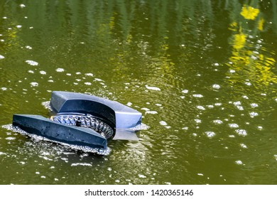 Beautiful and clean pond. Skimmer floats on surface of water in pond. Close-up. Skimmer collects leaves, dirt and other foreign objects from surface of water. There is place for text.