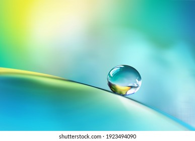 Beautiful clean transparent bright drop of water on smooth surface in blue and yellow colors, macro. Creative image of beauty of environment and nature.