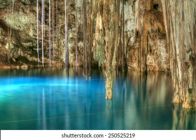 Beautiful clear blue water of Xkenken cenote in Dzitnup, Mexico illuminated from above with tree roots and stalactites hanging from ceiling of cavern
