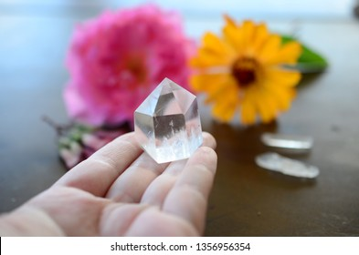 Beautiful Clear Quartz tower, and fresh pink rose flowers. Bright Quartz crystal, healing crystal photo with flowers. Hand holding quartz tower, crisp colors in natural lighting. Vibrant meditation.
