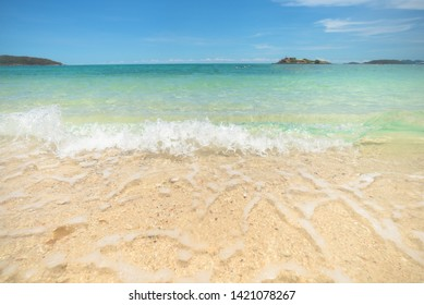 Beautiful clear sand beach and tropical light blue sea. Soft wave of blue ocean on sandy beach. Sallow water, Clear water. Seaside.