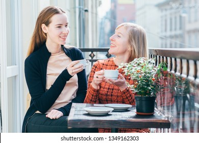Beautiful clever daughter - mother's pride. Two blond females - mature mother and adult daughter drinking coffee during breakfast at sunny morning. Mutual understanding, different generations concept.